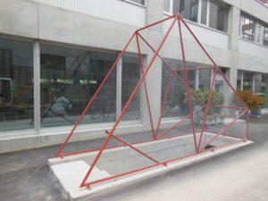 Rohrrahmen-Konstruktion über Treppenabgang zu Tiefgarage bespannt mit Geflecht