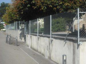 Geflechtzaun. Rohrpfosten mit angeschweisster Fussplatte an Mauer geschraubt.