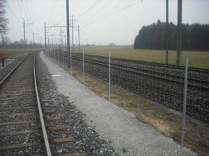 Knotengitter-Zaun entlang Bahngleis. Eingerammte StapleLok-Pfosten.
